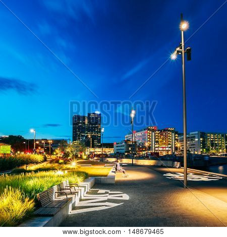 Oslo, Norway. The Scenic Cityscape In Bright Night Illumination With Quiet City Waterfront Foreground Under Blue Summer Sky.