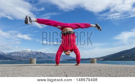 The young girl engaged in acrobatics at the pier. Montenegro. Spring 2016