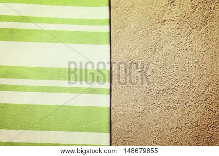 Top view of sandy beach with summer accessories with towel