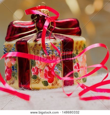 Close up of decorative Christmas ornaments in a a gift box with red ribbons. Christmas and New Year's concept.