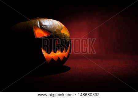 The carved face of pumpkin glowing on Halloween on red background