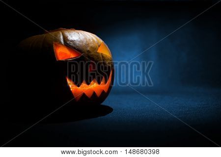 The Carved Face Of Pumpkin Glowing On Halloween On Blue Background