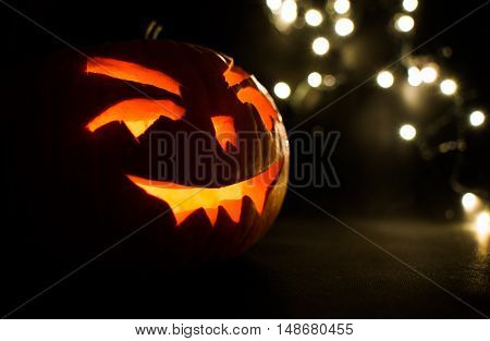 Carved Face Of Pumpkin Glowing On Halloween On Bokeh Light Background