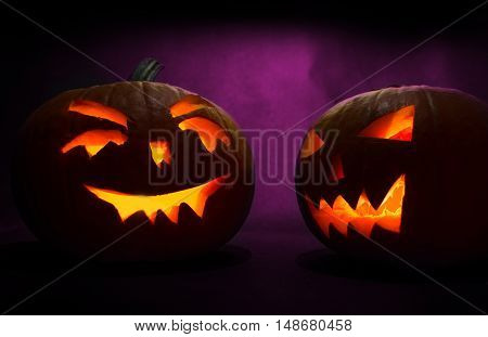 Two Carved Faces Of Pumpkins Glowing On Halloween On Purple Background