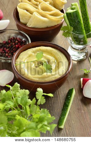 Healthy hummus dip with olive oil and pita bread and vegetables, vertical