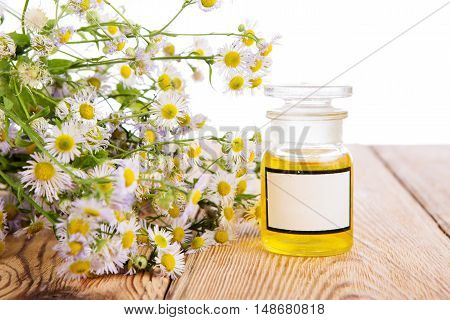 Massage Oil In A Glass Bottle With Camomile Flowers On Wooden Table