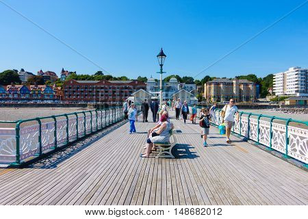 Penarth United Kingdom - August 15 2016: Tourists locals and families are walking towards the end of the Victorian Penarth Pier to catch the Balmoral ship which is about to leave for a day trip.