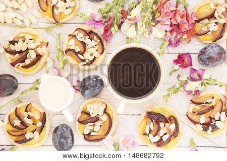 Plum tarts with the snapdragon flowers and a cup of coffee