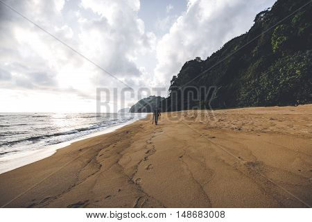 A man walking along beautiful beach only accompanied by nature.