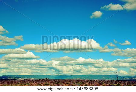Rural cloudscape with flat road and power lines in foreground and mountain range in background. Retro toned image.