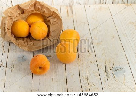 Several ripe apricots in the kraft bag on a wooden background