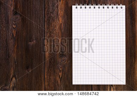 Blank notebook on a dark wooden background, copy space