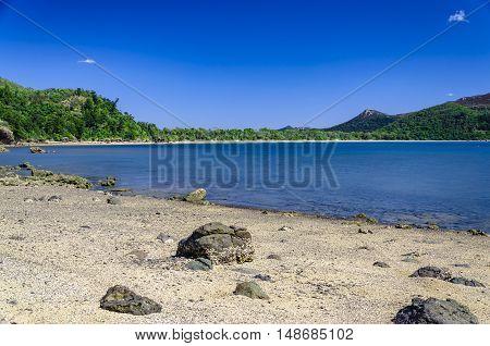 Sandy beach with rocks and tropical vegetation.