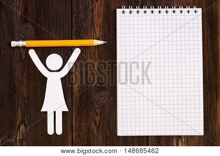 Paper woman with pencil and blank notebook, wooden background. Abstract conceptual image
