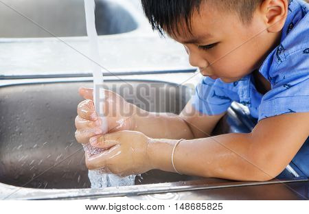 Asian boy is watching her hand with clean water
