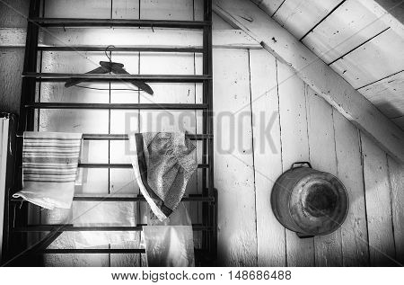 horizontal black and white image of a wood plank wall of the inside of a cabin with a drying rack with some items hanging from it and an old fashioned tin wash tub hanging on wall with room for text.