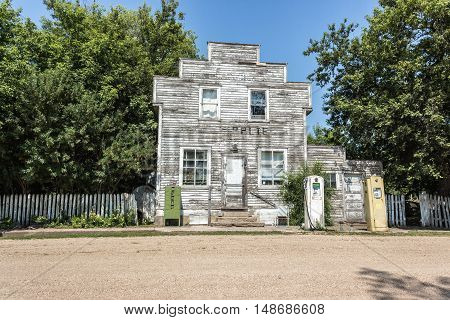 horizontal image of a very picturesque scene of an old abandoned wooden store with gas pumps sitting in front of a gravel road ,surrounded by trees on a warm summer day