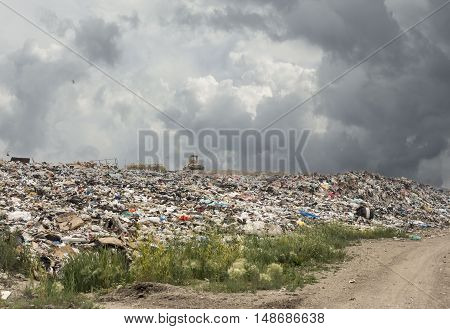 horizontal image of a huge landfill full of garbage and trash with a heavy duty machine operator sitting at the top under a very cloudy dark grey sky in the summer