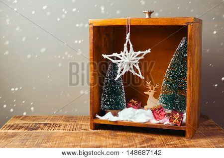 Christmas diorama with pine trees and decorations on wooden table