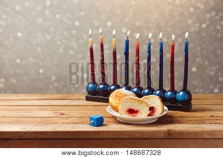 Jewish holiday hanukkah with sufganiyah and menorah on wooden table over bokeh background