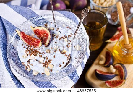 Dessert made with ricotta figs cashew nuts flax seed and honey. Selective focus.