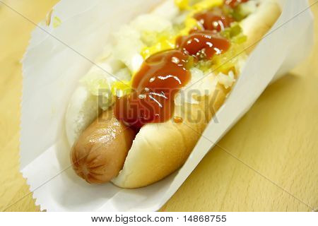Hotdog fastfood sausage in bun with condiments