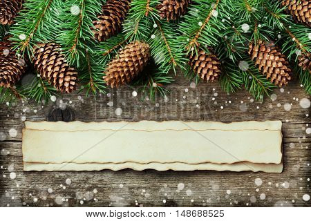 Christmas or New Year background of fir tree and conifer cone on old vintage wooden board, fantastic snow effect and aged paper with copy space for text, top view.