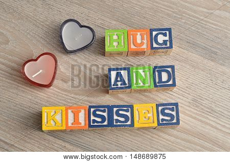 Valentine's Day. Hugs and kisses Spelled with colorful alphabet blocks and two red heart shape candles