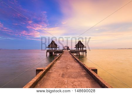 Dramatic sunset sky over walk way leading to ocean, natural landscape background