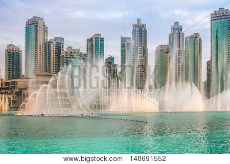 The Dubai Fountain, the world largest choreographed fountain on Burj Khalifa Lake, performs at sunset, to the beat of the selected music. On background, skyscrapers of Old Town Island near Dubai Mall.
