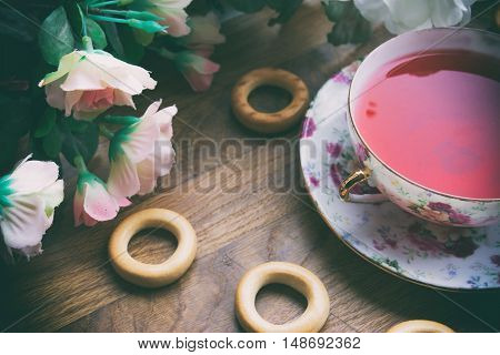 against the background of pink roses and drying tea cup