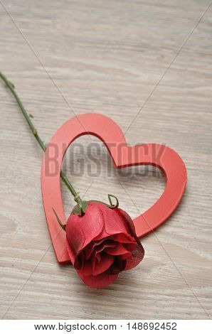 Valentine's Day. A single rose with a red wooden heart