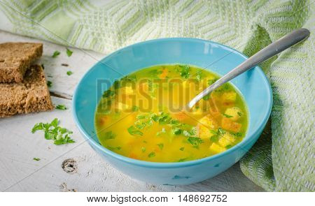 Zuppa Imperiale - Italian soup with eggs and Parmesan cheese dish of Emilia Romagna. Imperial soup on wooden table. Omelet in chicken broth with parsley in a bowl. Italian cuisine concept.