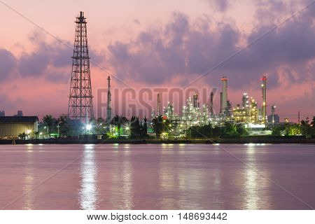 Oil refinery river front night view, industrial background