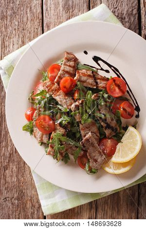 Straccetti Grilled beef with arugula and tomatoes close-up