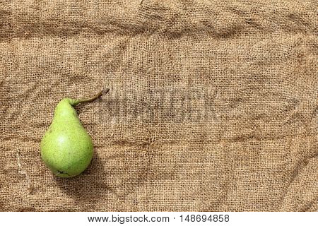 pear lying on a crumpled rough burlap top view / first harvest of the season