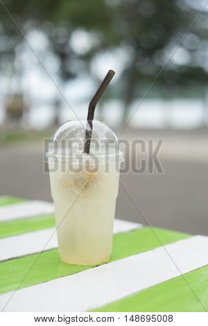 iced plum juice in takeaway cup on wooden table,blurred sea in background,selective focus