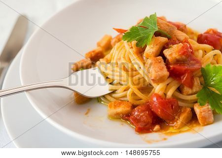 Closeup of spaghetti with fish and little tomatoes with some leaves of parsley