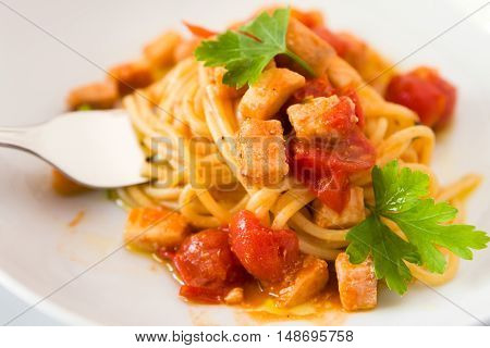 Closeup of spaghetti with fish little tomatoes and parsley