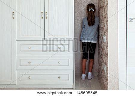 Little girl standing in the corner of her room behind the cupboard