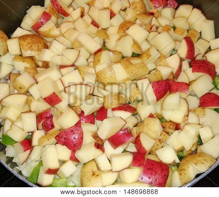 A pan full of potatoes peppers onions and ham being fried up for a dinner snack