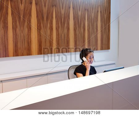 Brunette receptionist young woman in desk talking phone