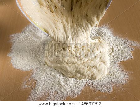 Raw wheat dough for pizza and bread on wooden background