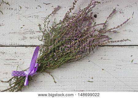 Heather bouquet on white wood background right