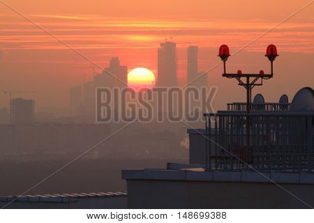 A large disk of the sun at sunset between city skyscrapers under construction