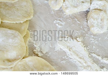 The dough rolled with circles sprinkled flour. Making of pierogi with Cherry.