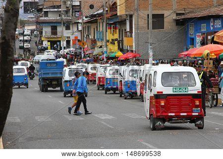 Cajamarca Peru - September 23 2016: Two boys cross street with moto-taxi traffic in Cajamarca Peru on September 23 2016