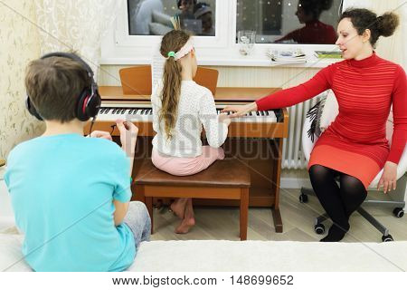 three people in room: mother teaches daughter to play keyboard, son sitting on bed in his head headphones
