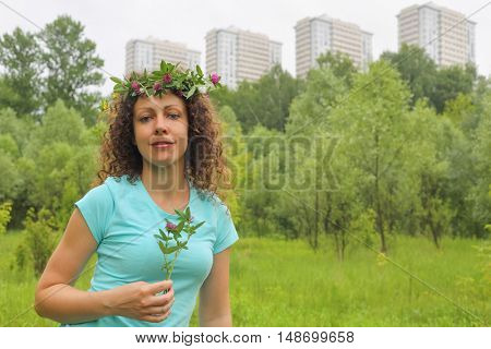 half length portrait of young woman with wreath of flowers urban wooded area near apartment complex, holding clover