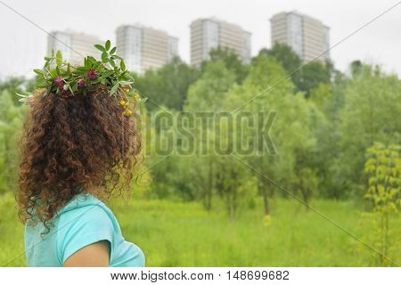 half length portrait of young woman with wreath of flowers urban wooded area near apartment complex, holding clover, photo from back